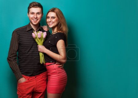 Young couple in love holding a bouquet of tulips.