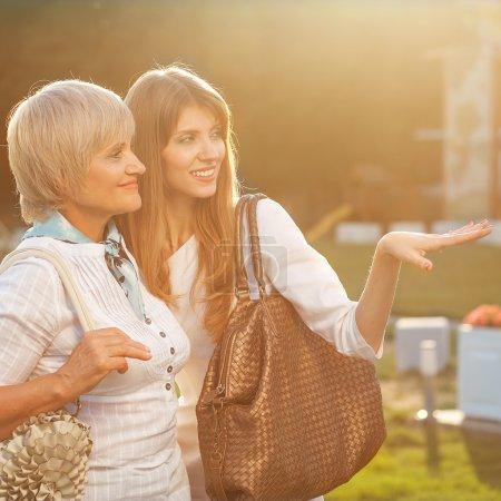 Photo pour Adulte mère et fille après le shopping à pied vers le bas de la rue et de parler - image libre de droit