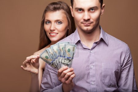 Loving couple are holding a large sum of money. Business concept