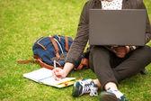 Estudiante de moda joven sentada en el césped en el parque y explotación