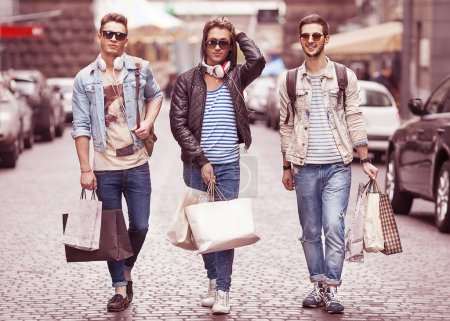 Three Young male fashion metraseksuals shop. Men shopping walk.