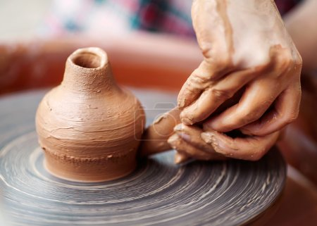 Potter hands making in clay on pottery wheel.