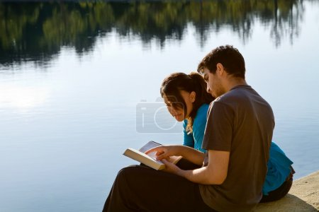 Photo pour Deux jeunes adultes assis au bord d'un lac et étudiant la Bible (King James Version ) - image libre de droit