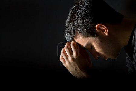 Photo for Young man praying in the dark - Royalty Free Image