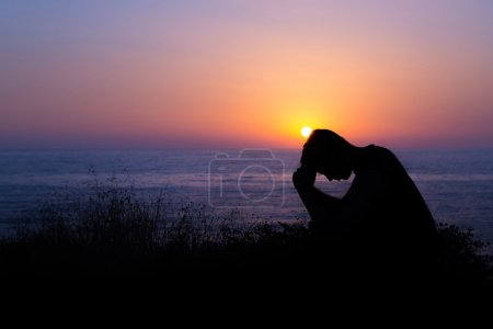 Photo for Young man praying to God during sunset by the sea - Royalty Free Image