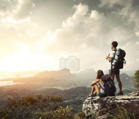 Photo for Hikers with backpacks enjoying valley view from top of a mountain - Royalty Free Image