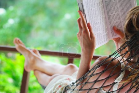Photo for Woman lying in a hammock in a garden and enjoying a book reading - Royalty Free Image