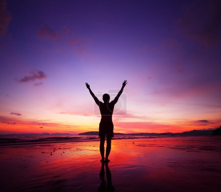 Young man standing on tropical beach with raised hands at sunset