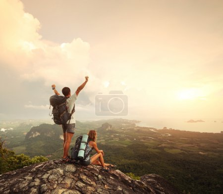 Photo for Two hikers with backpacks standing on top of a mountain with great valley view - Royalty Free Image