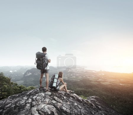 Photo for Hikers with backpacks standing on top of a mountain and enjoying a valley view - Royalty Free Image