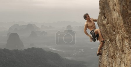 Photo for Young man climbing vertical wall with valley view on the background - Royalty Free Image