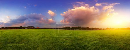 Photo for Green wide meadow with grass and colorfull cloudy sky at sunset - Royalty Free Image
