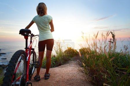 Photo pour Jeune femme avec vélo debout sur le sol et en admirant le coucher de soleil sur mer - image libre de droit
