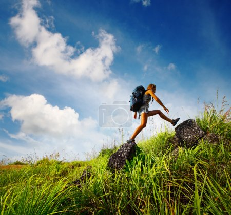 Photo for Tourist with backpack crossing rocky terrain with grass at sunny day - Royalty Free Image