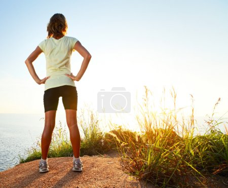 Photo for Young slim lady worn traning clothes standing on countryside path and enjoying sunset - Royalty Free Image