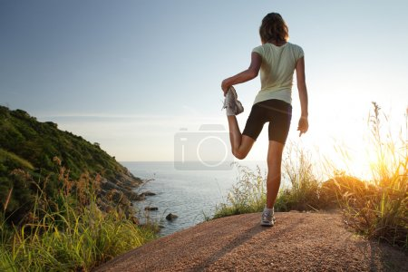 Photo for Cross country racer stretching on top of a hill and enjoying sunset sea view - Royalty Free Image