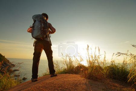 Photo for Hiker with backpack standing on a rock and enjoying sunset over sea - Royalty Free Image