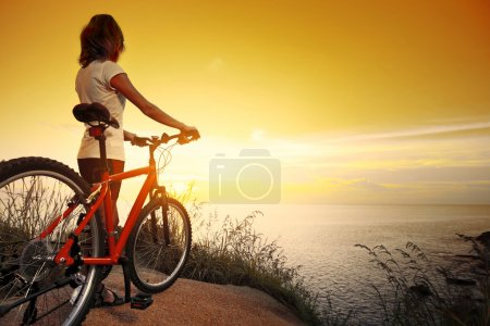 Photo for Young lady standing on top of a hill with bicycle and enjoying the sunset over sea - Royalty Free Image
