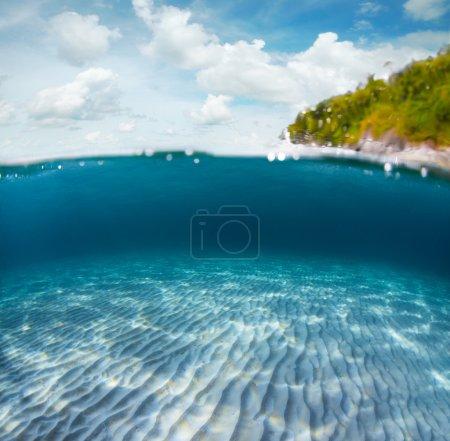 Photo pour Pousse sous-marine d'un fond marin sablonneux et île tropicale verte avec ciel nuageux au-dessus de la surface de la mer - image libre de droit