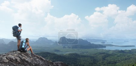 Photo for Two tourists with backpacks relaxing on top of a mountain and enjoying valley view - Royalty Free Image