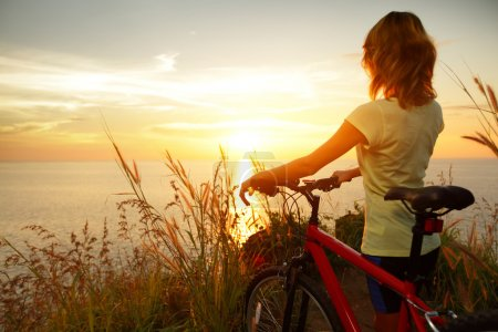 Photo for Young lady standing with bicycle on a sea coast and enjoying sunset - Royalty Free Image