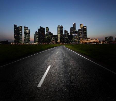 Foto de Carretera de asfalto y la ciudad con los edificios iluminados en el horizonte - Imagen libre de derechos