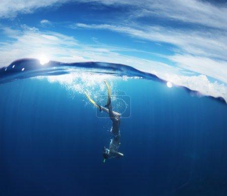 Photo pour Jeune femme plongée avec tuba et plongée sur une haleine tenir dans une mer tropicale claire avec ciel bleu avec soleil et nuages sur une surface - image libre de droit