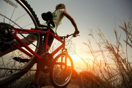 Photo for Young lady with bicycle on a rural road with grass - Royalty Free Image