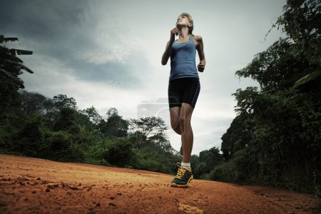 Photo for Young lady running on cross country road with earphones - Royalty Free Image
