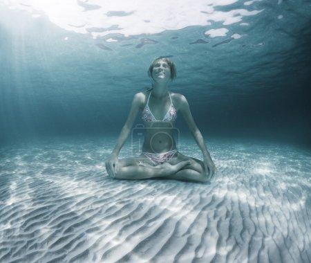 Photo pour Jeune femme assise sur un fond de sable marin en position lotus et retenant un souffle - image libre de droit