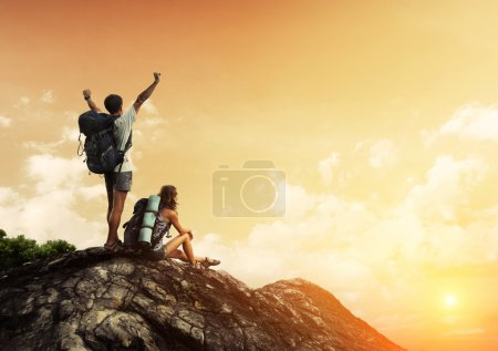 Photo for Two hikers with backpacks enjoying sunset view from top of a mountain - Royalty Free Image
