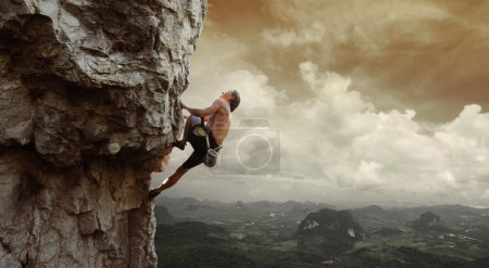 Photo for Young man climbing natural rocky wall with tropical valley on the background - Royalty Free Image