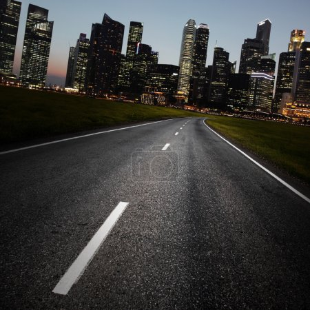 Photo for Asphalt road and a city with illuminated buildings on the horizon - Royalty Free Image