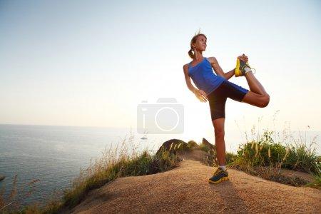 Photo pour Jeune femme mince faisant des exercices d'étirement sur un chemin rural avec de l'herbe - image libre de droit