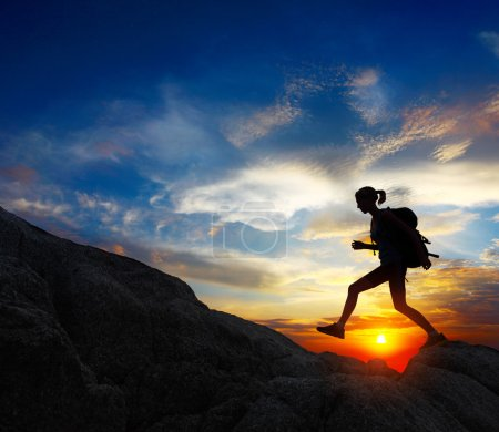 Photo for Hiker with backpack jumping over rocks with sunset sky on the background - Royalty Free Image