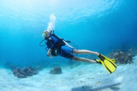 Photo pour Tournage sous-marin d'un plongeur nageant dans une eau bleu clair près d'un fond - image libre de droit