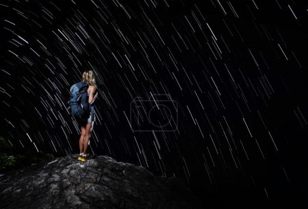 Photo for Hiker with backpack standing on top of a mountain with star trails on the backgound (real stars) - Royalty Free Image