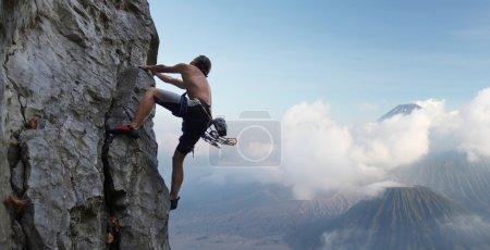 Photo pour Jeune homme escaladant une paroi rocheuse naturelle avec les volcans sur le fond - image libre de droit