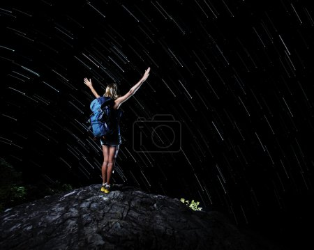 Photo for Hiker with backpack standing on top of a mountain with raised hands and looking at night sky with startrails - Royalty Free Image