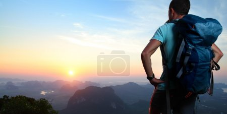 Photo for Hiker with backpack standing on top of a mountain and enjoying sunrise. - Royalty Free Image