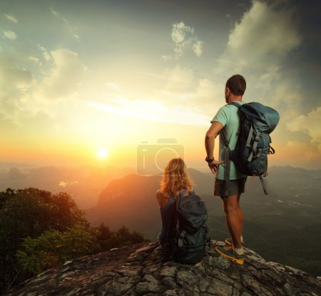 Photo for Tourists with backpacks enjoying sunrise on top of a mountain - Royalty Free Image