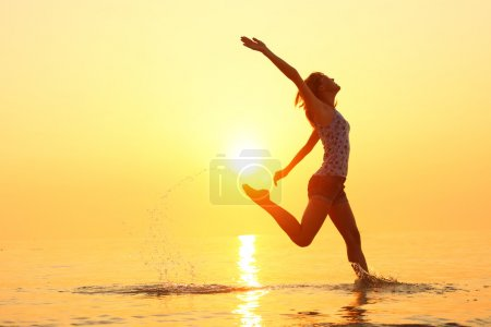 Lady running and jumping on a beach