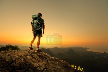 Photo for Hiker with backpack standing on top of a mountain and enjoying sunrise - Royalty Free Image