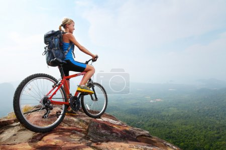 Photo for Young woman athlete standing on top of a mountain with red bicycle and enjoying valley view - Royalty Free Image