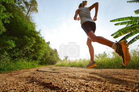 Photo for Young lady running on a rural road - Royalty Free Image