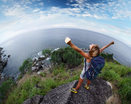 Photo for Hiker with raised hands standing on top of a mountain - Royalty Free Image