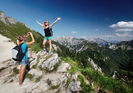 Photo pour Jeunes femmes avec des sacs à dos prenant des photos avec les Alpes sur le fond - image libre de droit