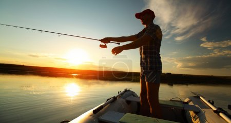 Photo for Man fishing from a boat at sunset - Royalty Free Image