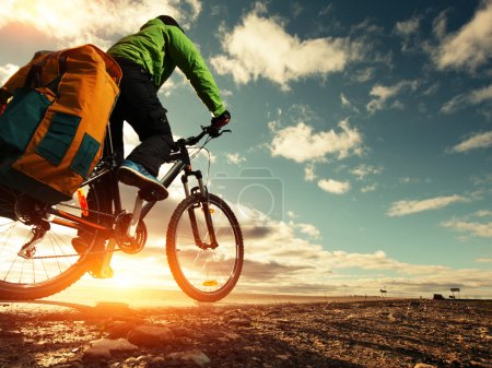 Photo for Bicycle tourist with loaded bike riding on an empty road - Royalty Free Image