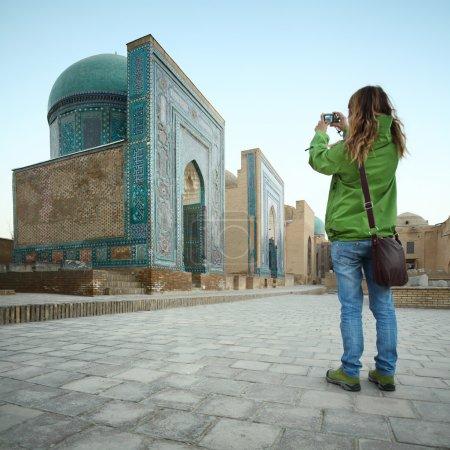 Photo pour Touriste jeune femme prenant une photo de l'ancien complexe de Shah i Zinda. Concentre-toi sur les bâtiments. Samarkand, Ouzbékistan - image libre de droit